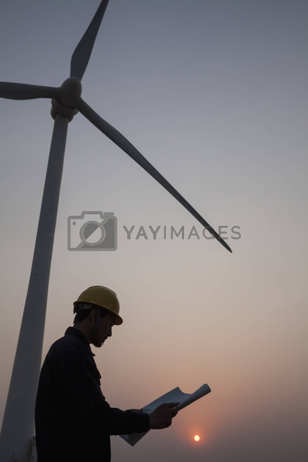 Silhouette of young male engineer holding a blueprint and standing beside a wind turbine at sunset