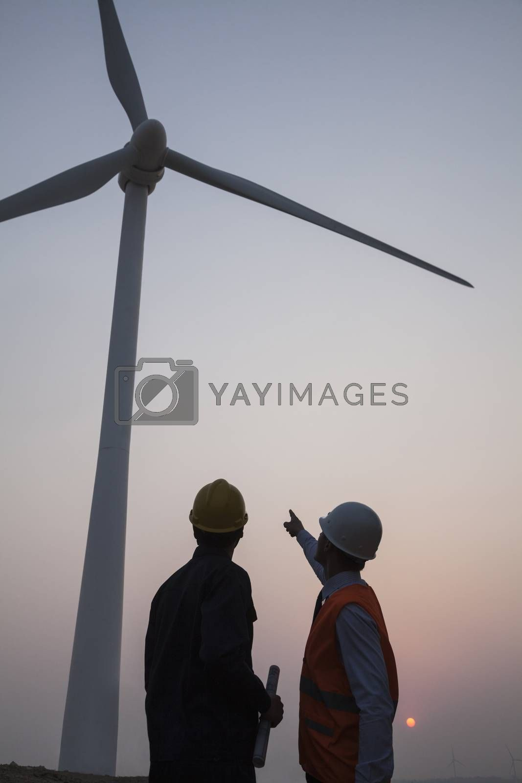 Two young male engineers standing beside a wind turbine at sunset, pointing up  by XiXinXing