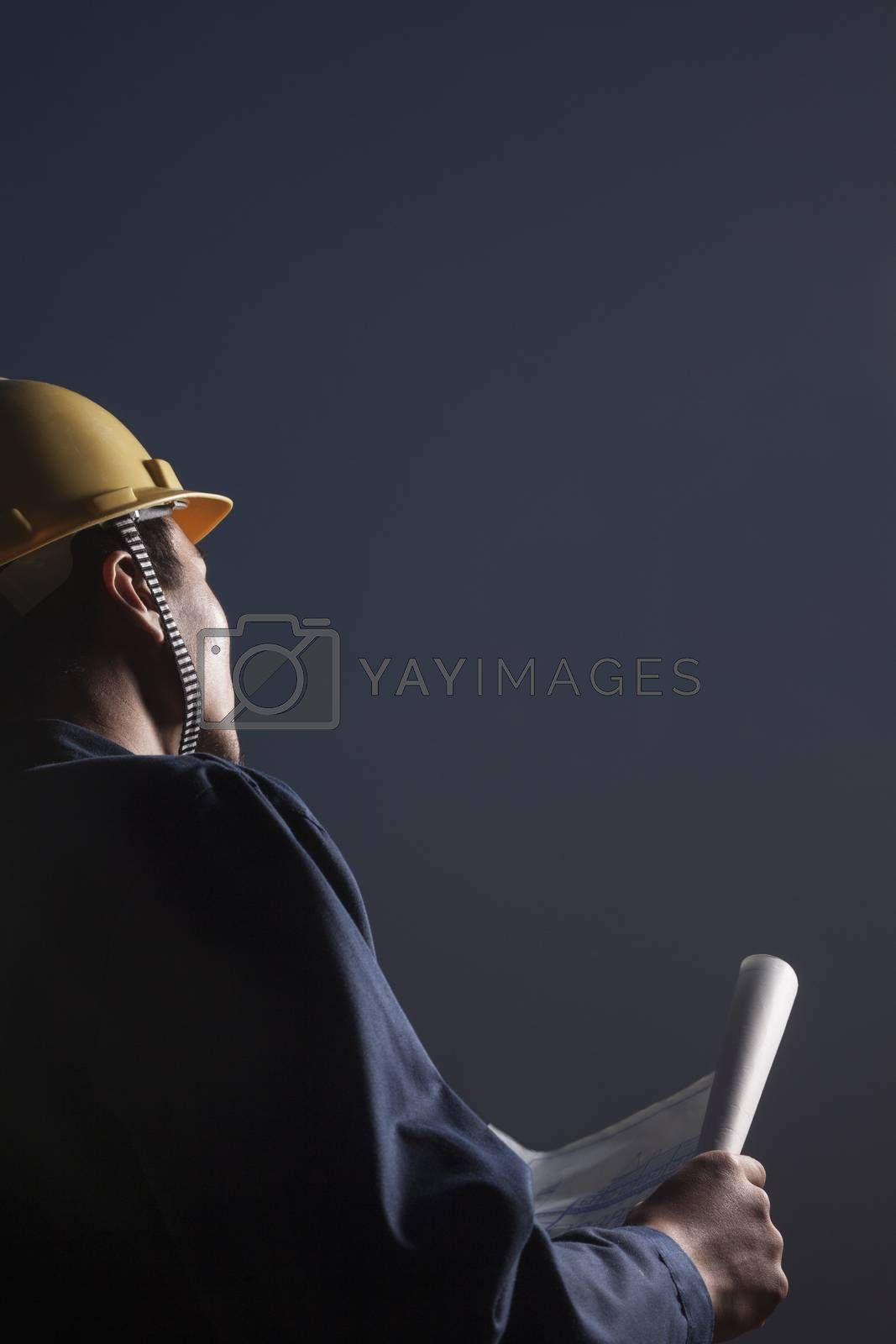 Young male engineer in a hardhat holding a blueprint at dusk, rear view by XiXinXing