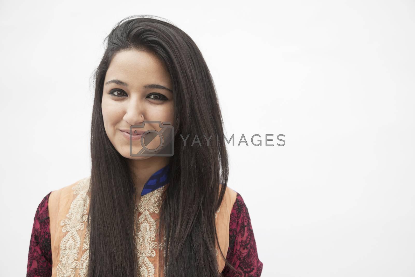 Portrait of smiling young woman wearing traditional clothing from Pakistan, studio shot by XiXinXing