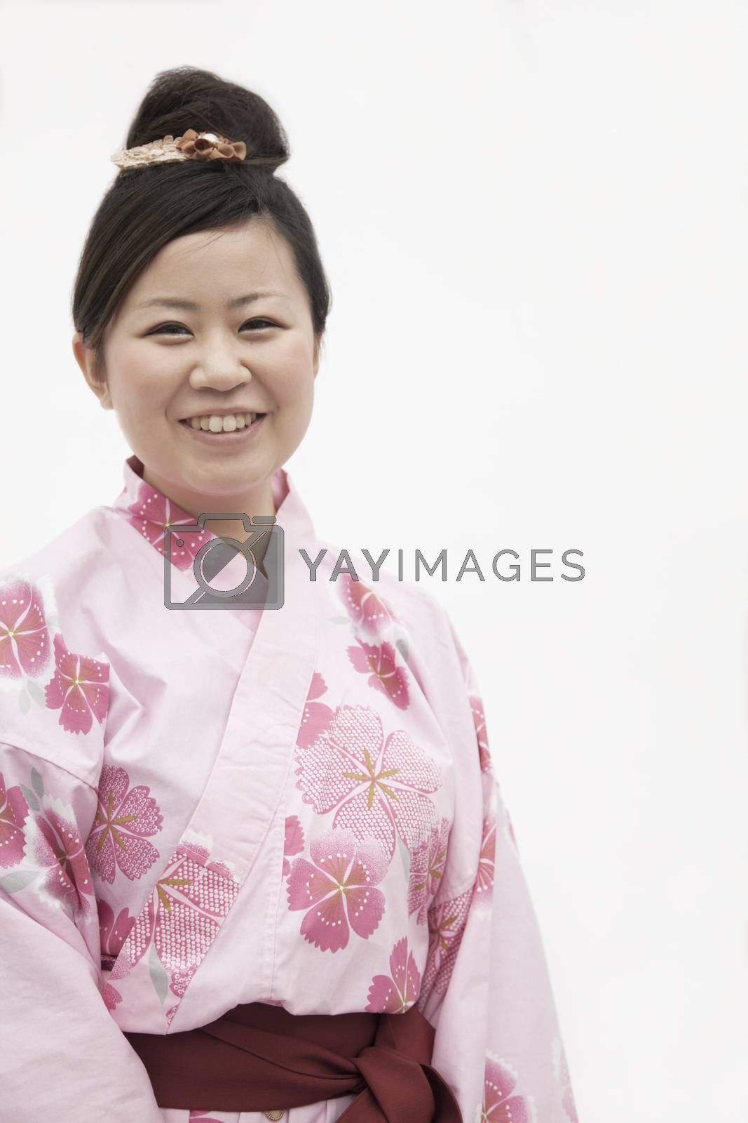 Portrait of young smiling woman in a pink Japanese kimono, studio shot