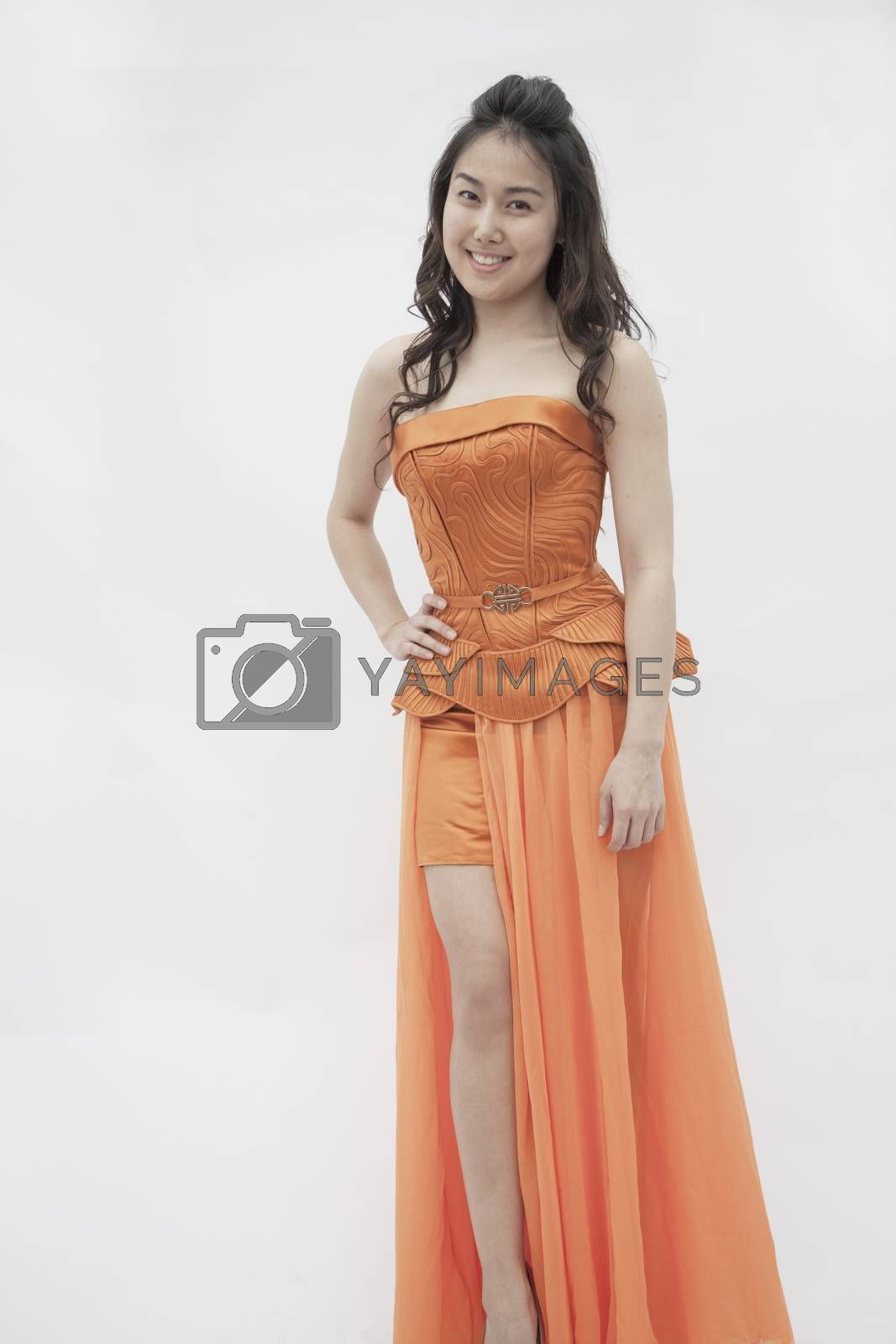 Portrait of young smiling woman with hand on her hip in an orange dress, studio shot