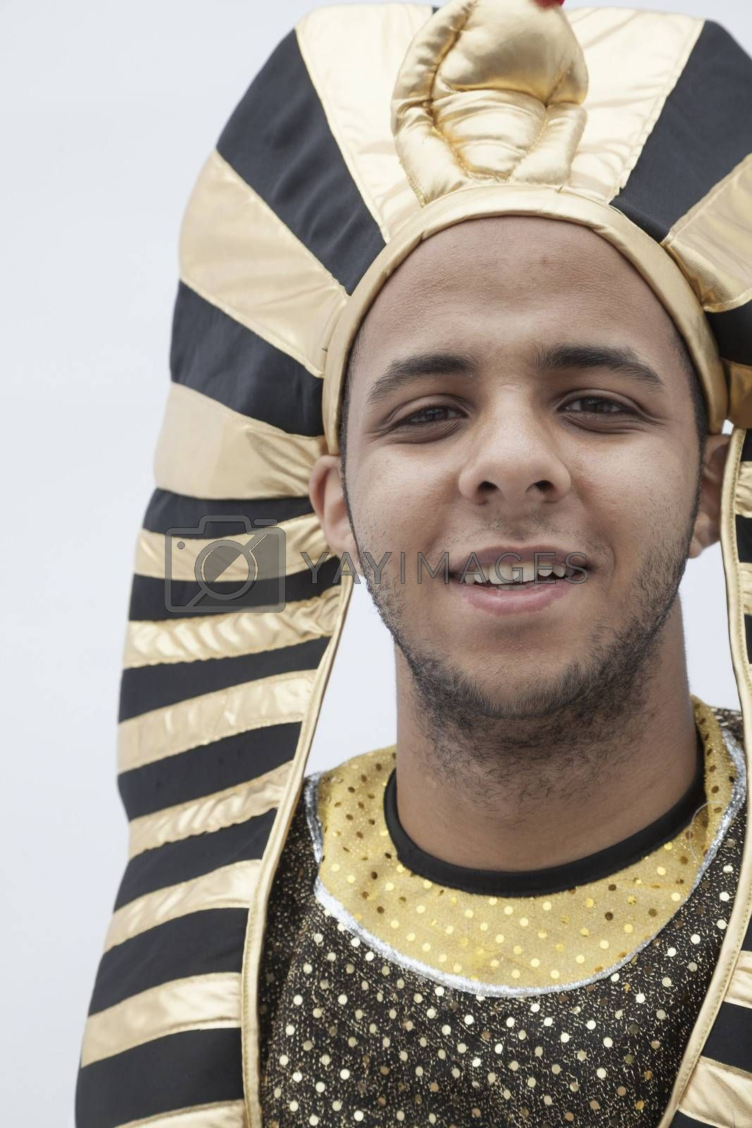 Portrait of smiling young man wearing a headdress from ancient Egypt, studio shot by XiXinXing