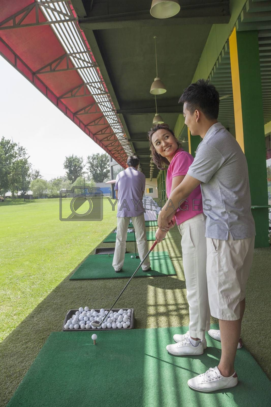 Young man teaching his girlfriend how to hit golf balls, arm around, side view