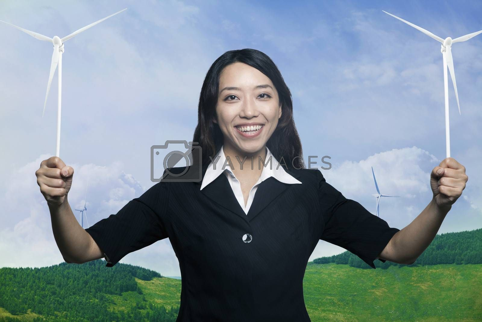 Young smiling woman holding to wind turbines and looking at camera