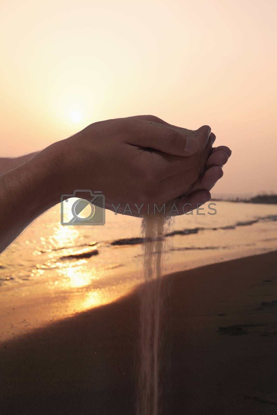 Hands holding and spilling sand with beach at sunset in the background
