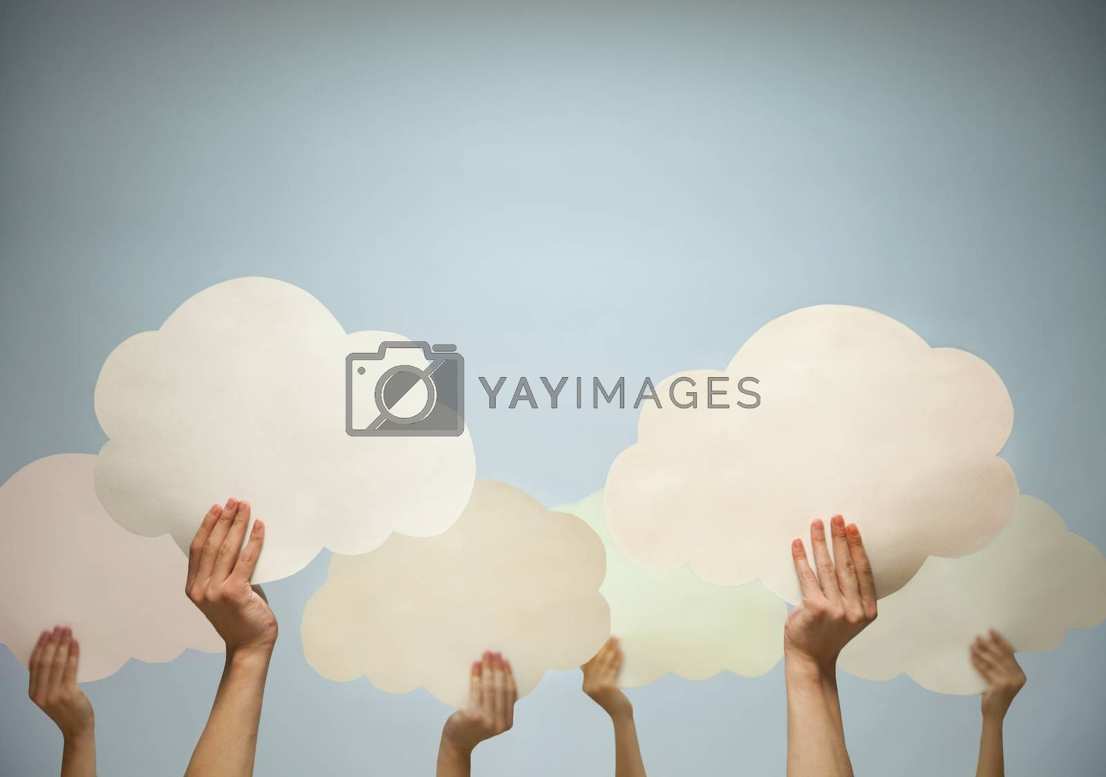 Multiple hands holding cut out paper clouds against a blue background, studio shot