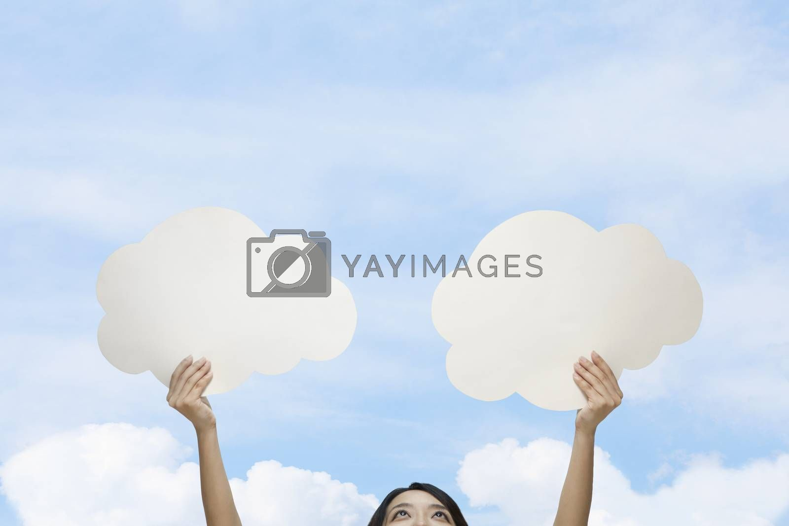 Young woman holding two cut out paper clouds against a blue sky with clouds by XiXinXing