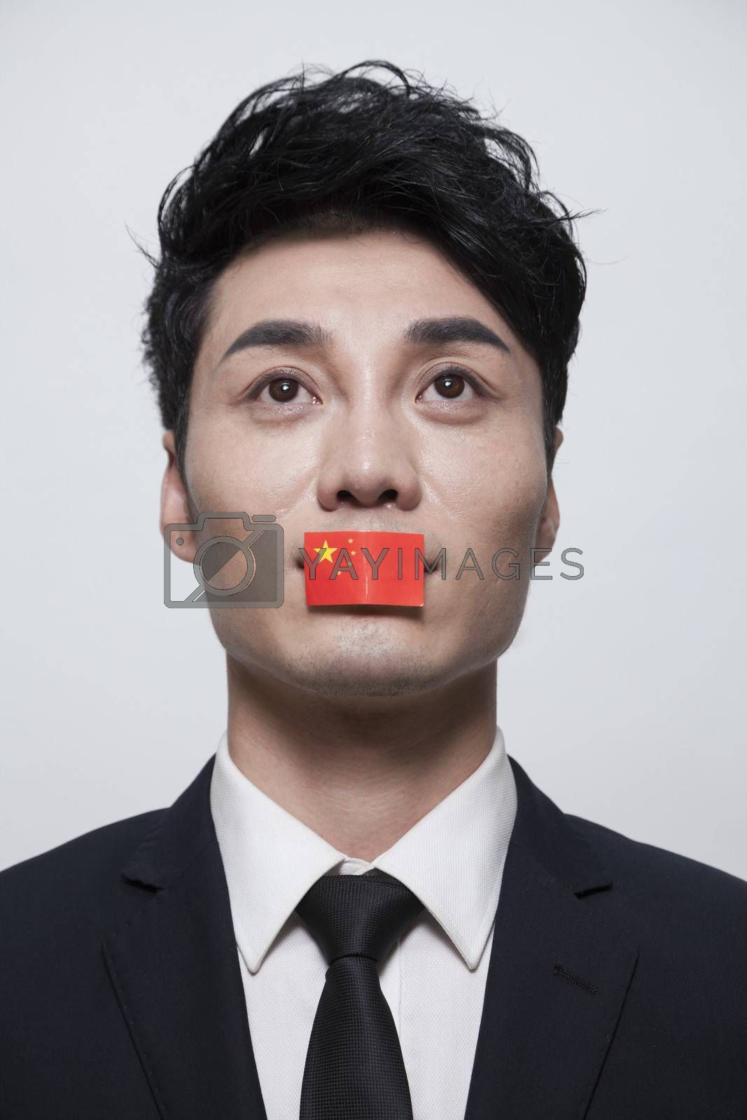 Young businessman looking up with a Chinese flag covering his mouth