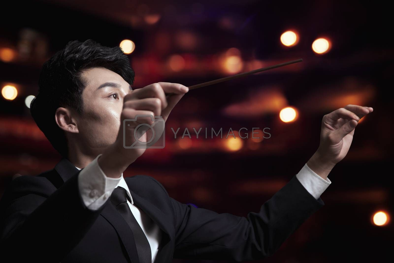 Young conductor with baton raised at a performance  by XiXinXing