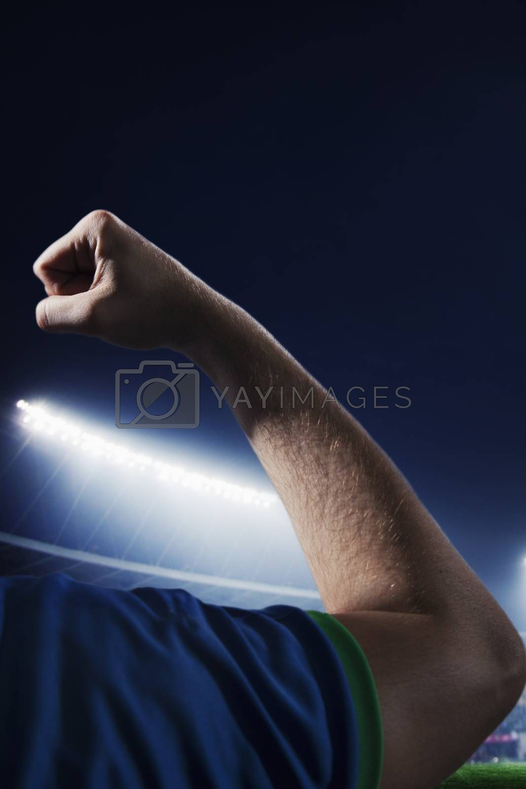 Soccer player flexing bicep in a stadium at night time