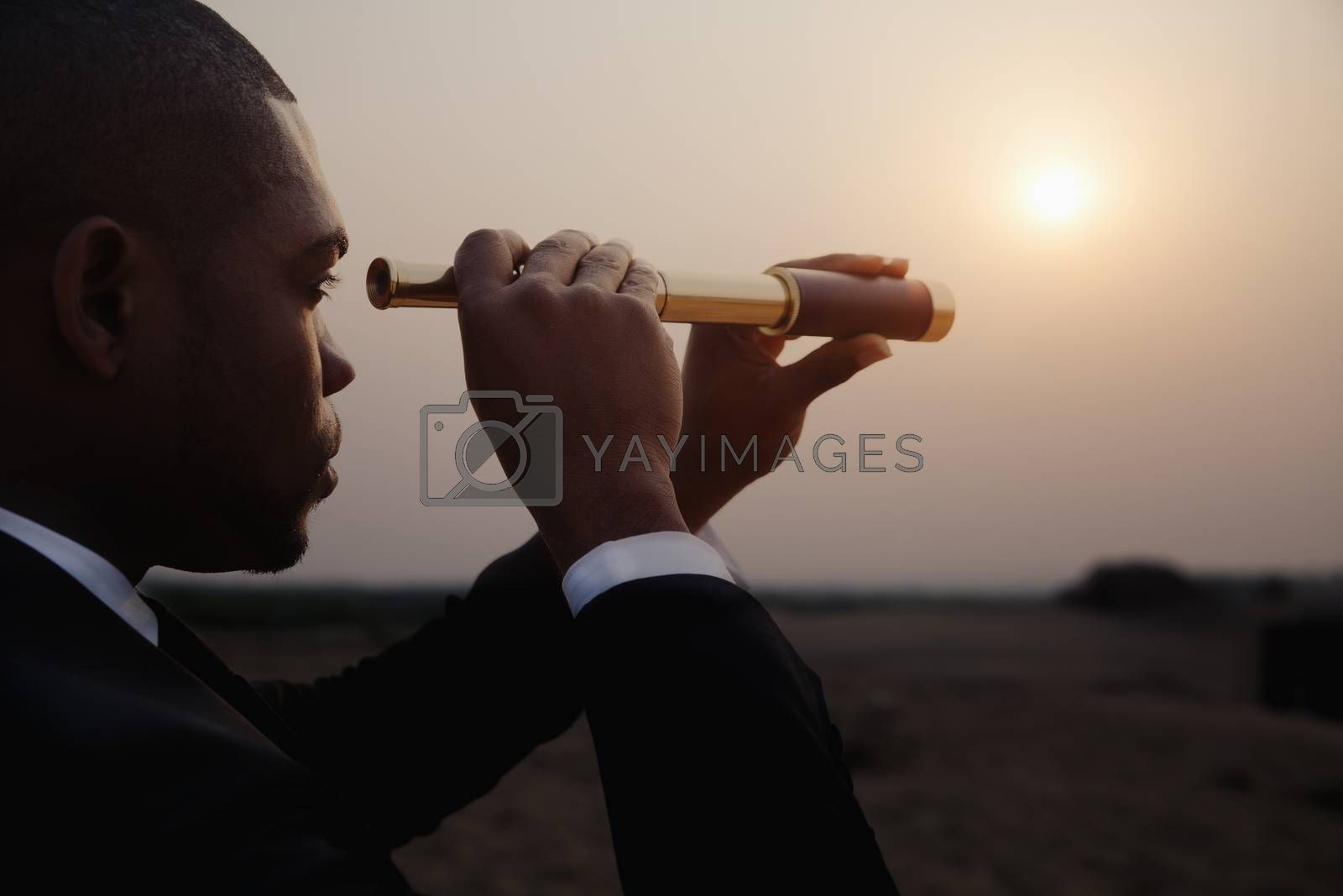 Young businessman looking through telescope in  the middle of the desert by XiXinXing