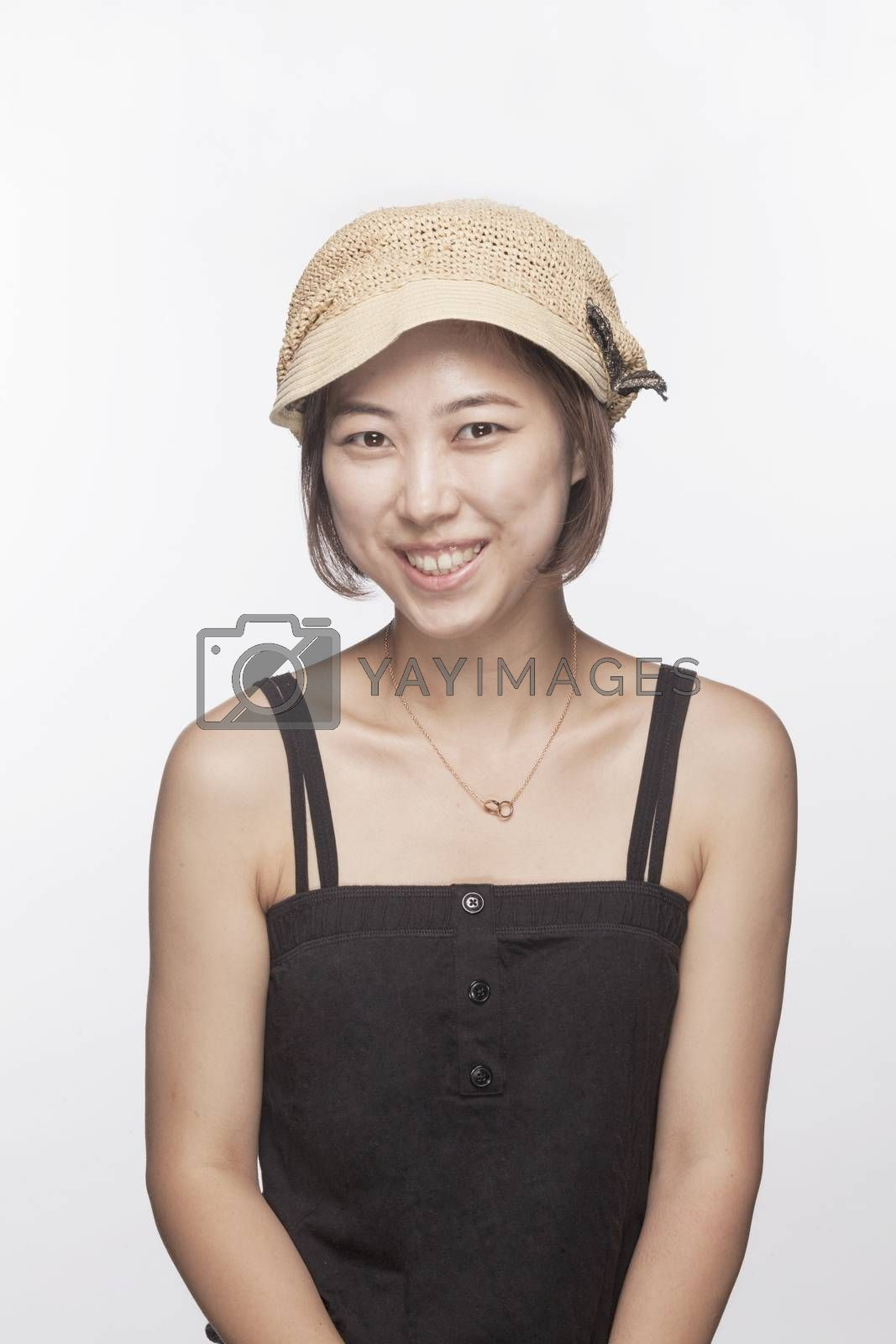 Portrait of smiling woman with hat, studio shot
