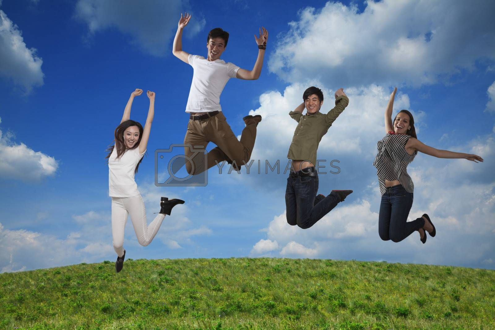 Four smiling friends jumping in mid-air, sky and cloud background