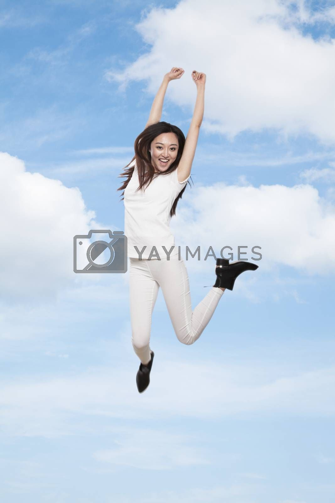 Young smiling woman jumping in mid-air, sky and cloud background