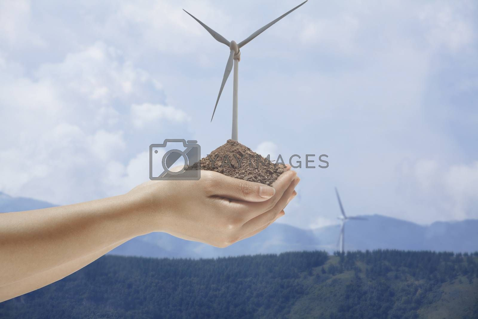 Hands holding soil with a wind turbine growing out from the middle