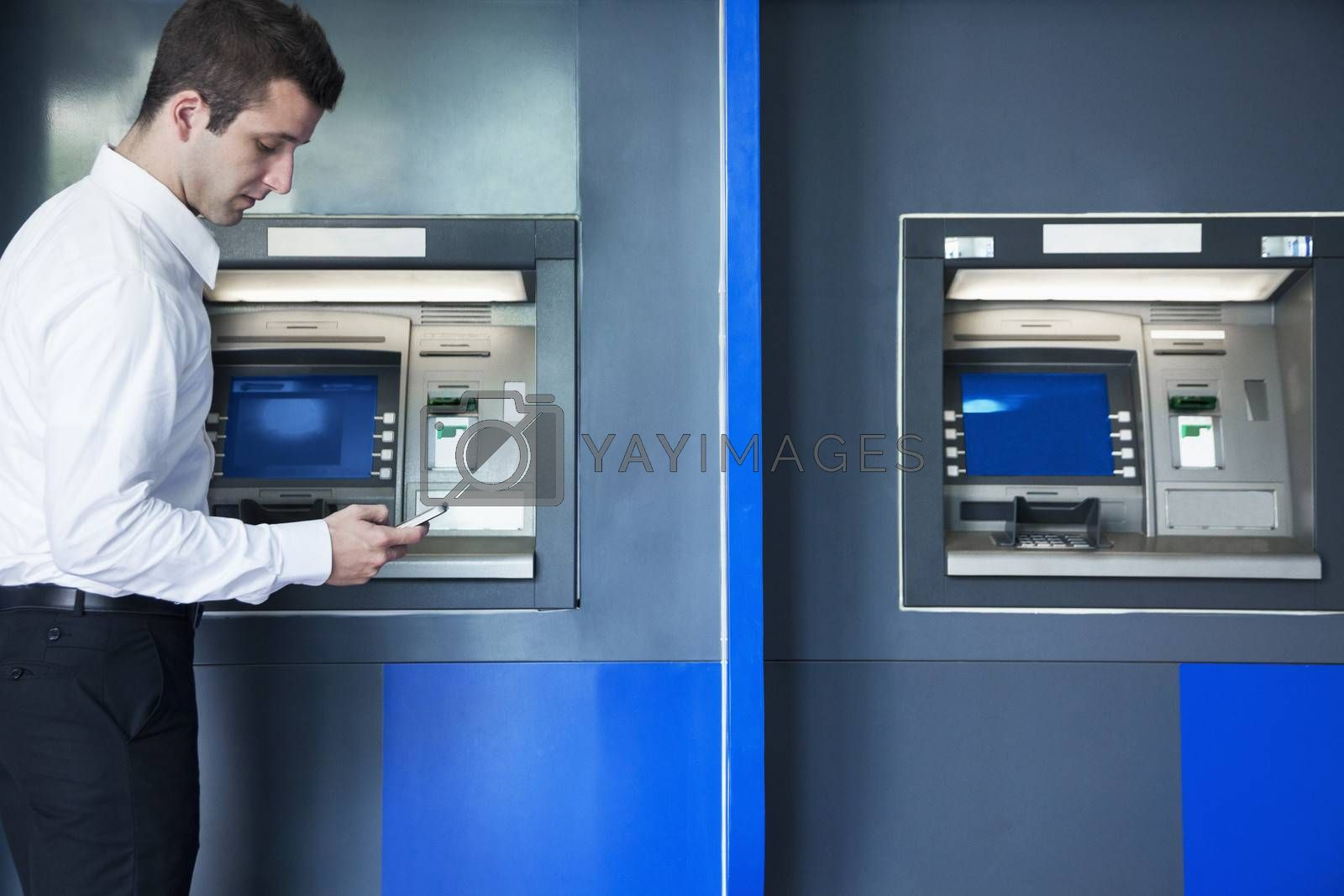 Young businessman taking out money from the ATM and looking down at his phone