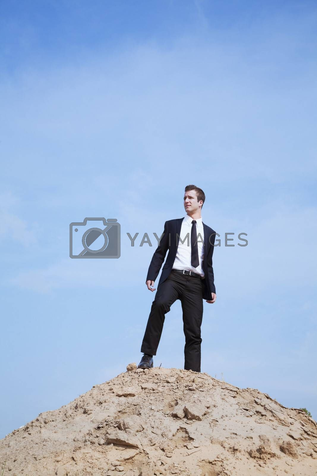 Young solitary businessman standing on a hill in the desert