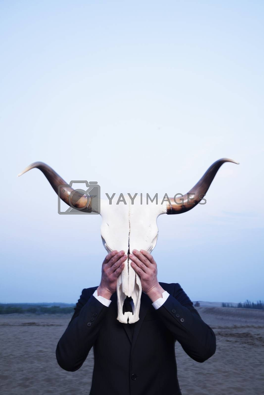 Businessman holding an animal skull in front of his face in the desert