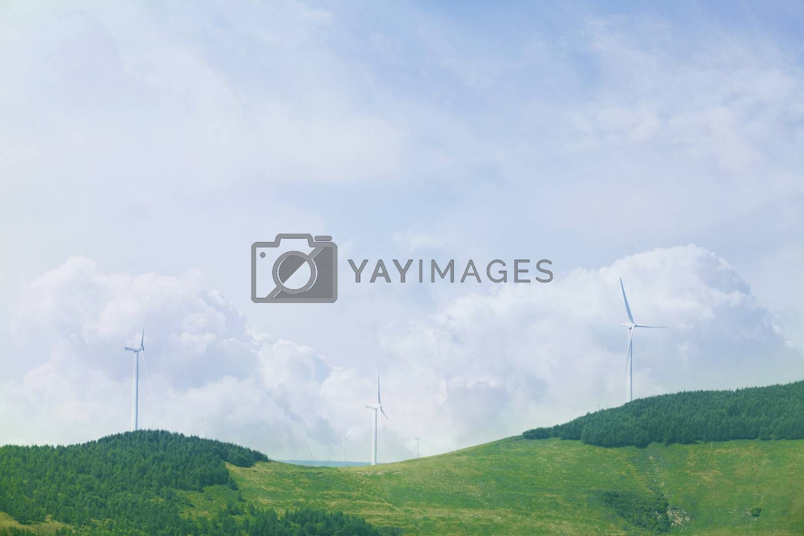 Wind turbines on lush, green, landscape with clouds.