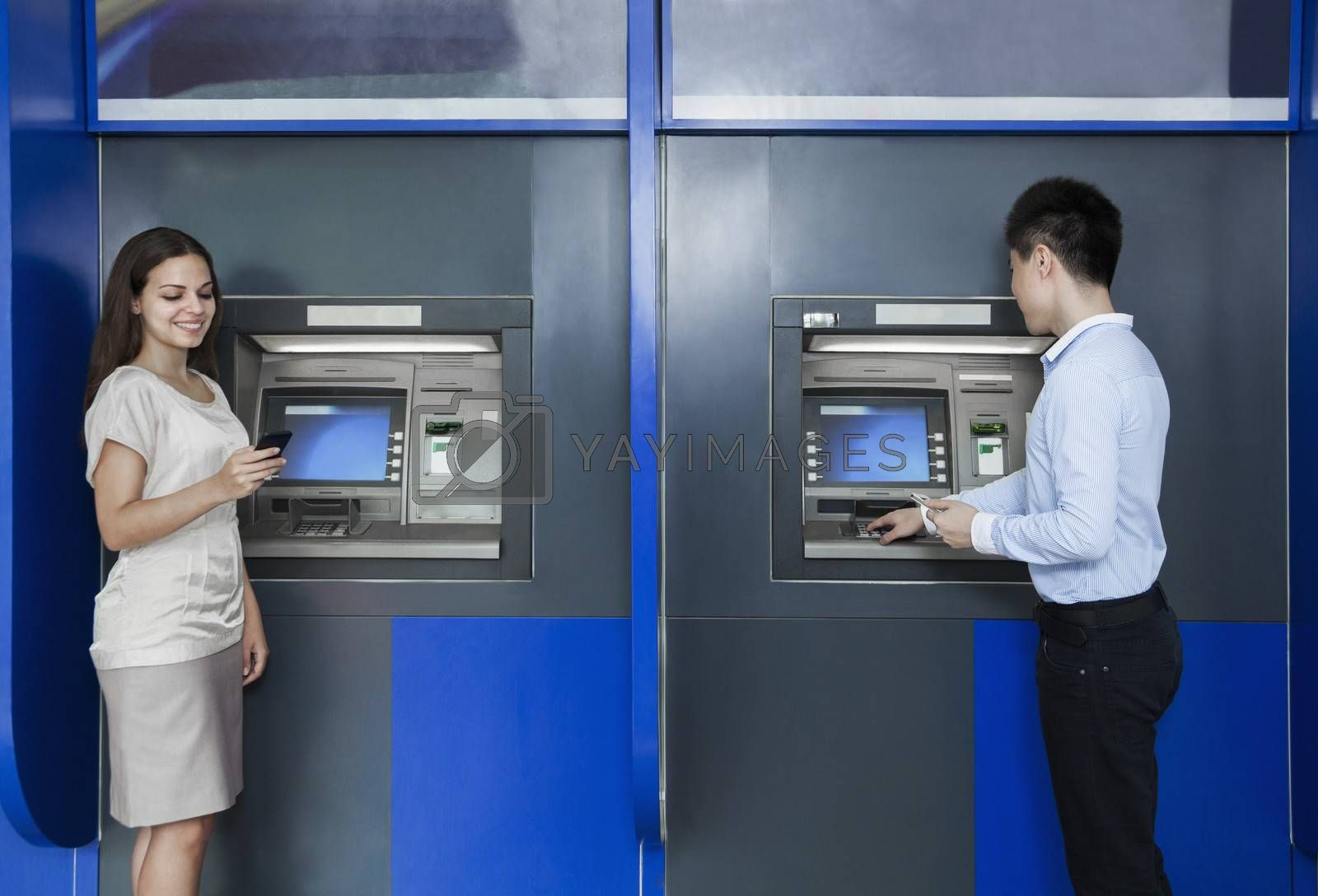 Two people standing and withdrawing money from an ATM