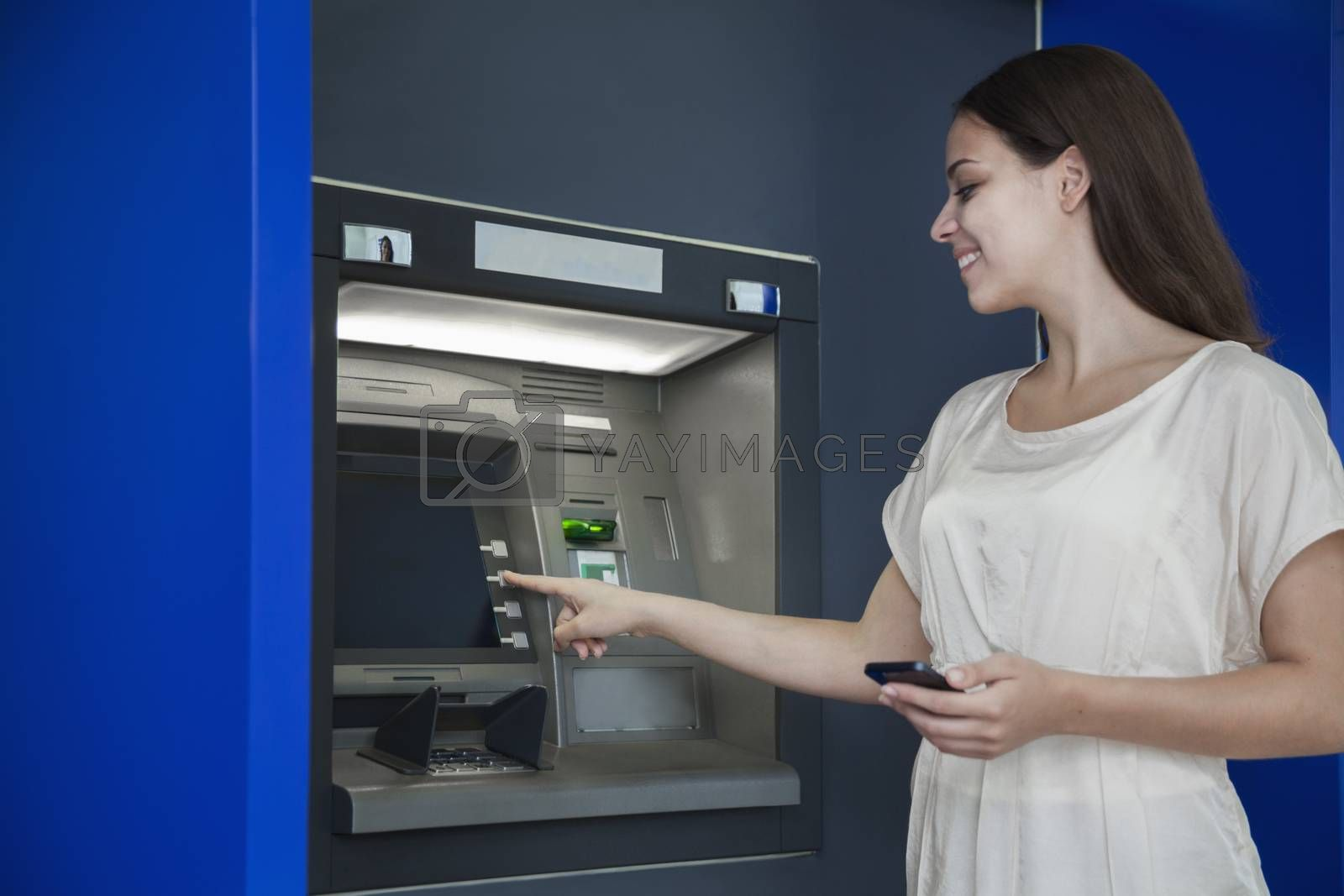 Smiling young woman withdrawing money from the ATM