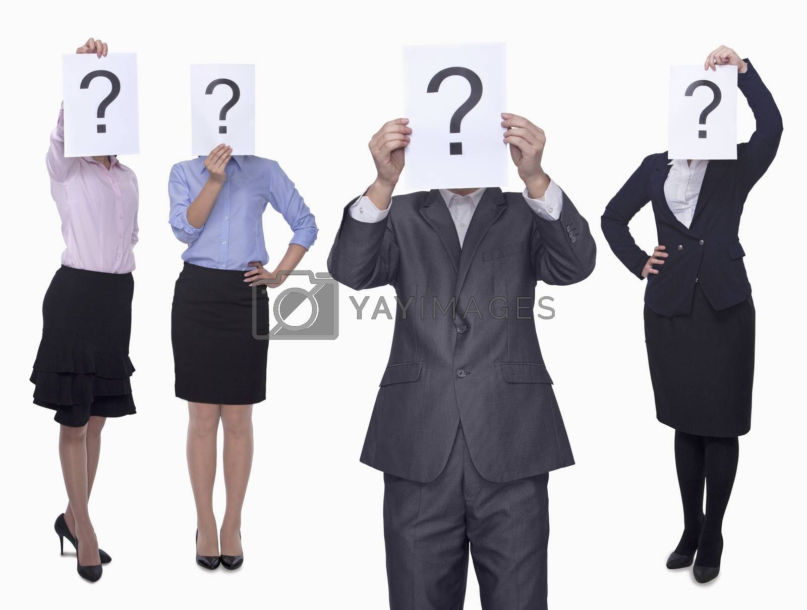 Four business people holding up paper with question mark, obscured face, studio shot by XiXinXing