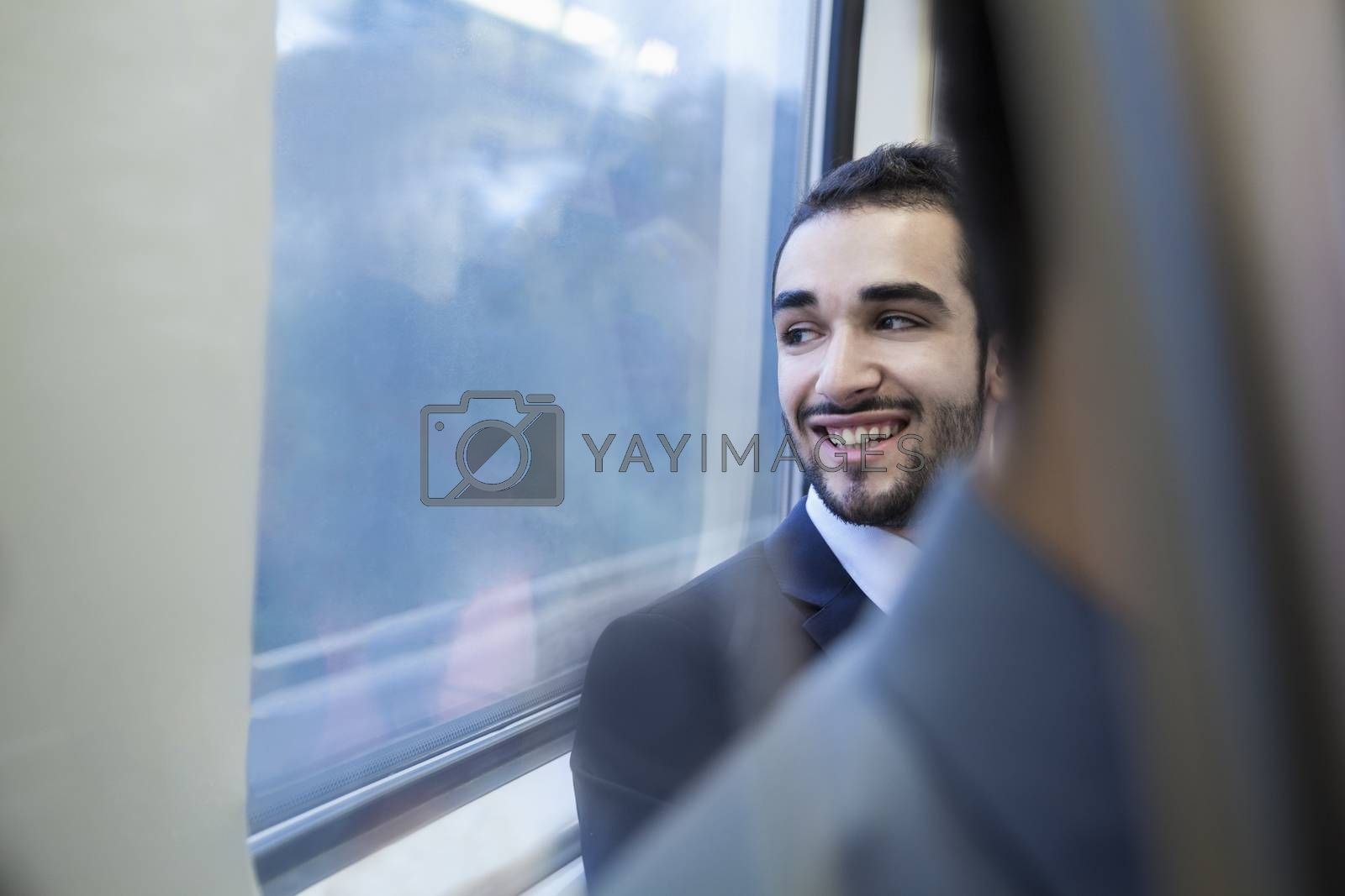 Young businessman smiling and looking out the window of the subway