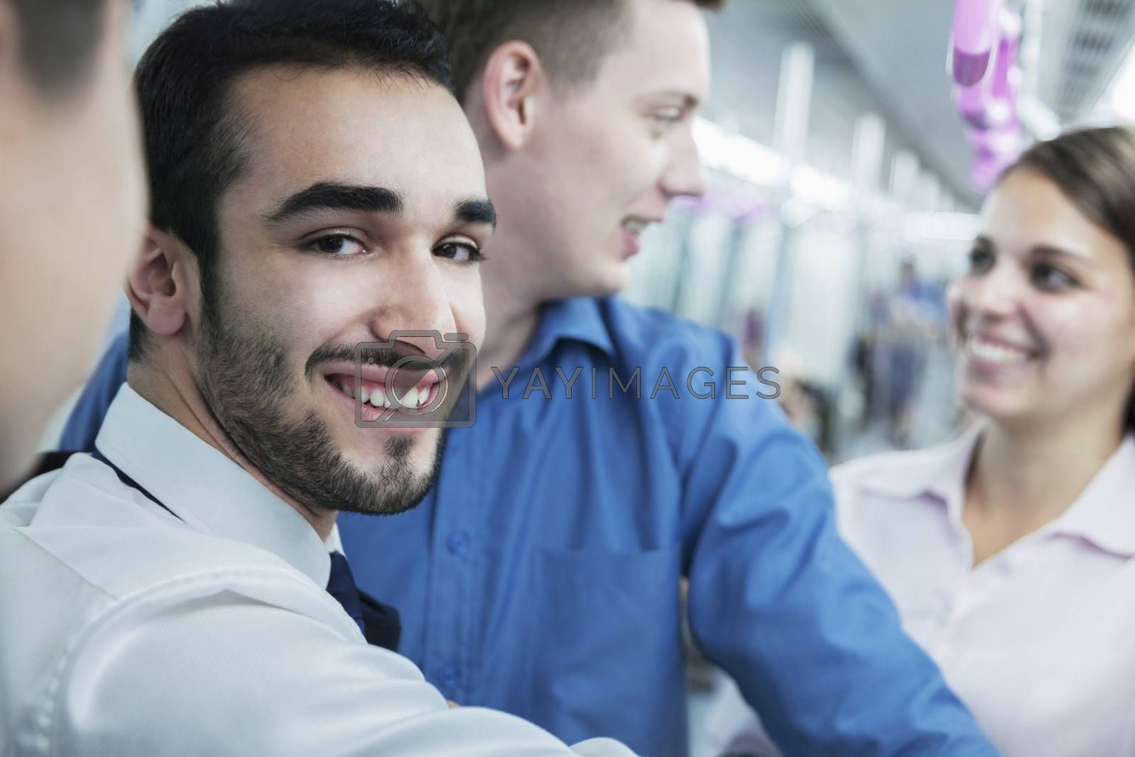 Portrait of young smiling businessman standing on the subway, looking at camera  by XiXinXing