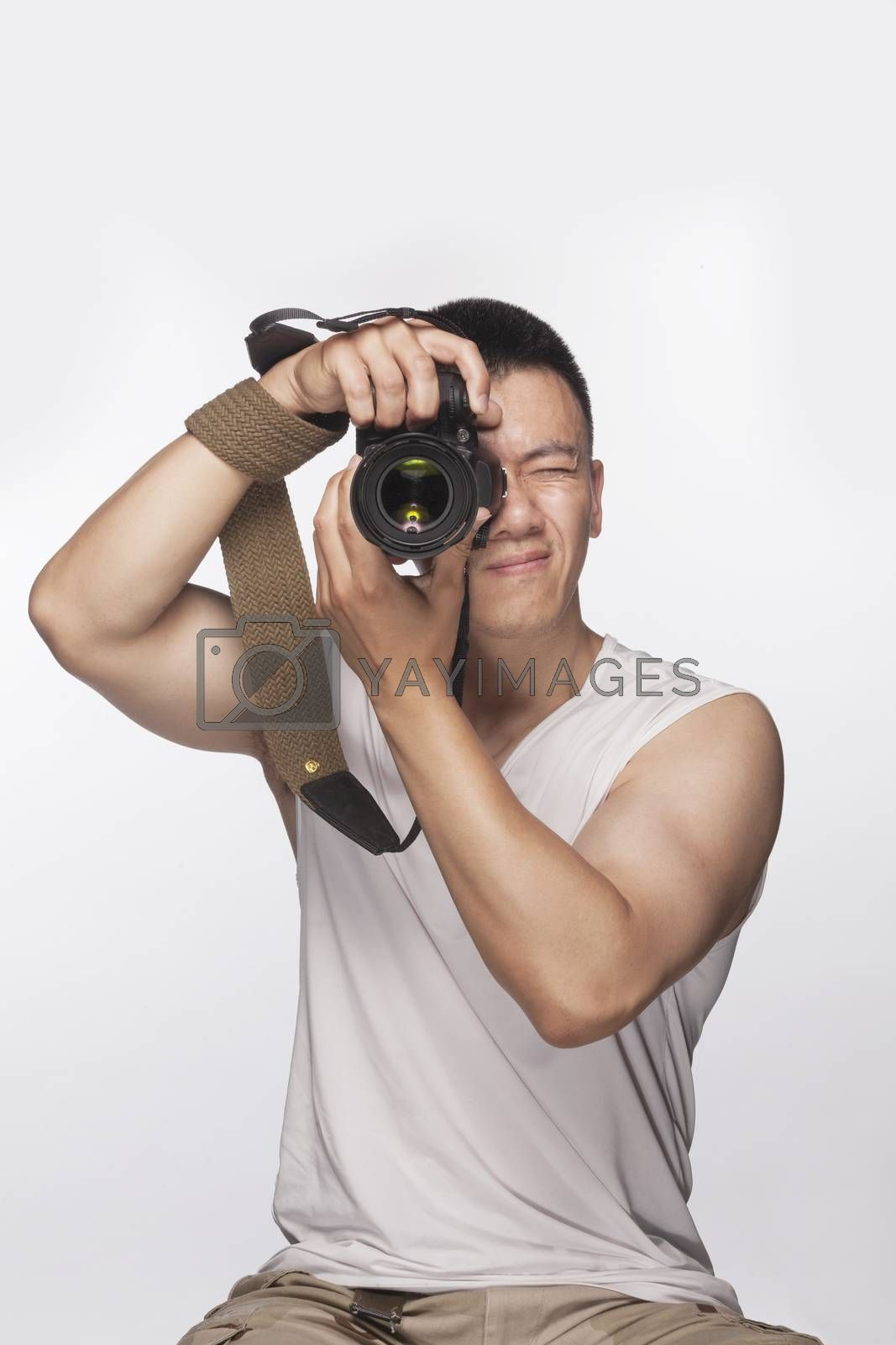 Man holding a camera and taking a photograph, studio shot by XiXinXing