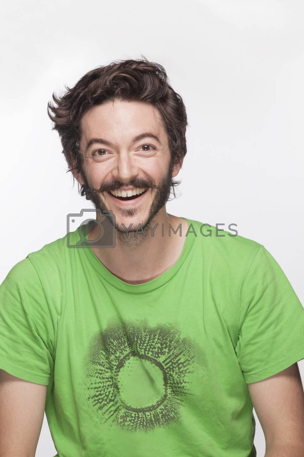 Smiling young man with beard and moustache looking at camera, studio shot