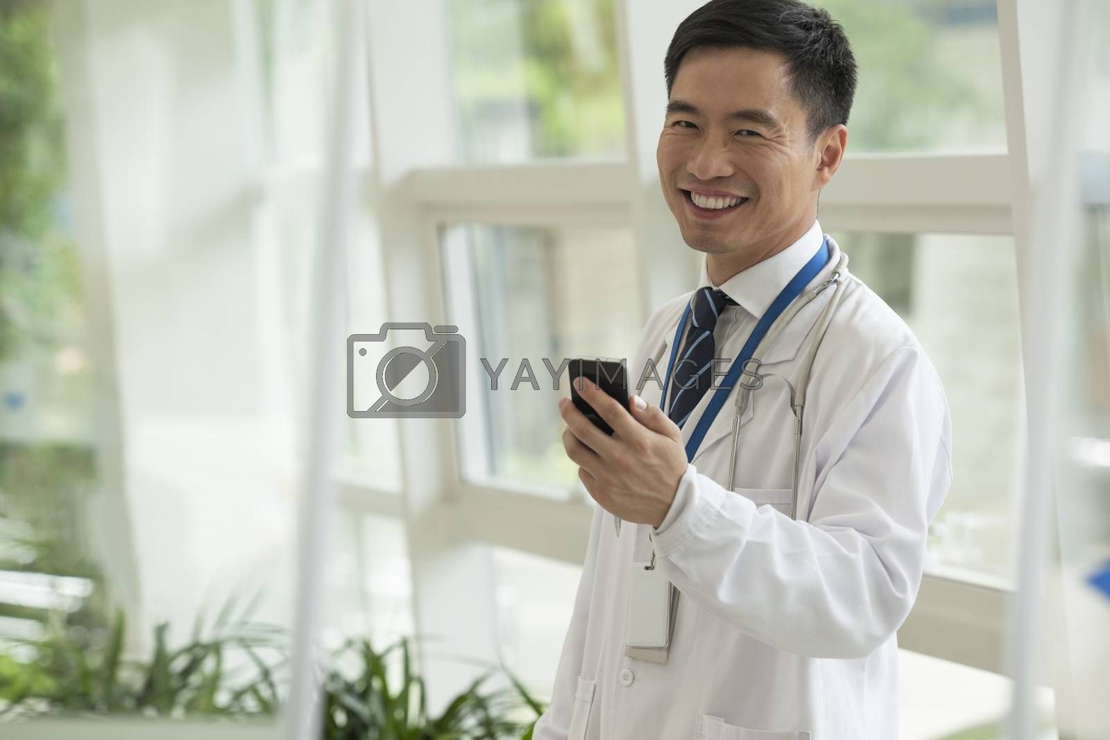 Smiling doctor using his phone in the hospital lobby, looking at camera, glass doors