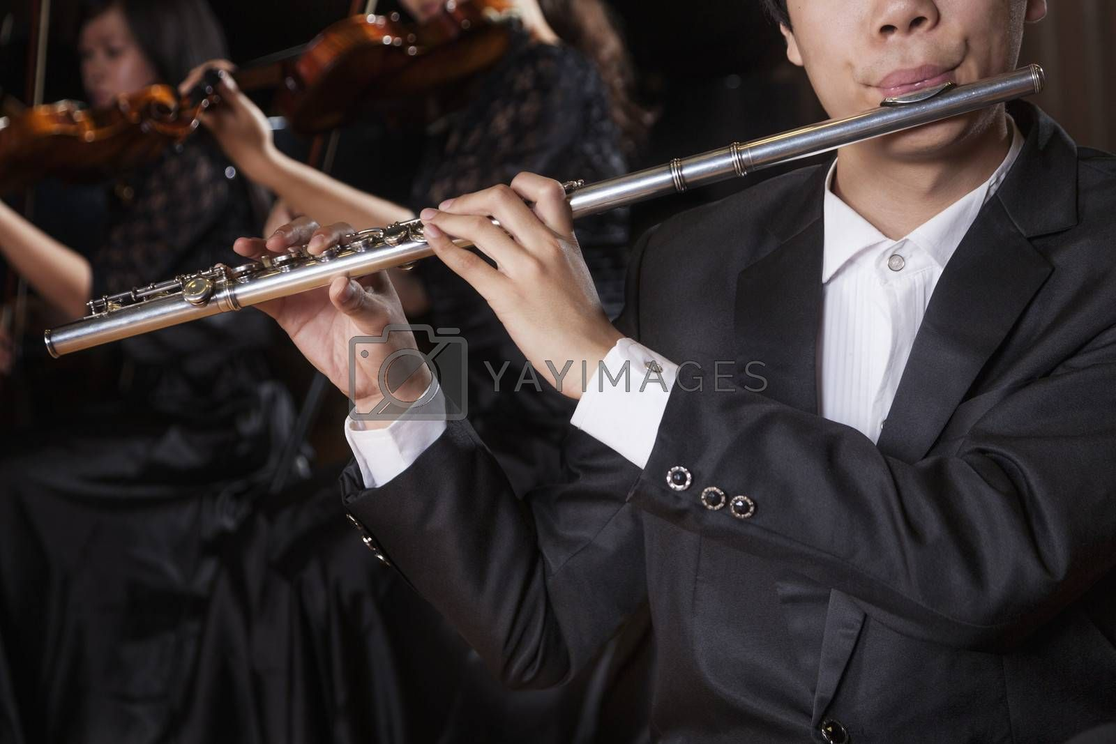 Flautist holding and playing the flute during a performance, close-up