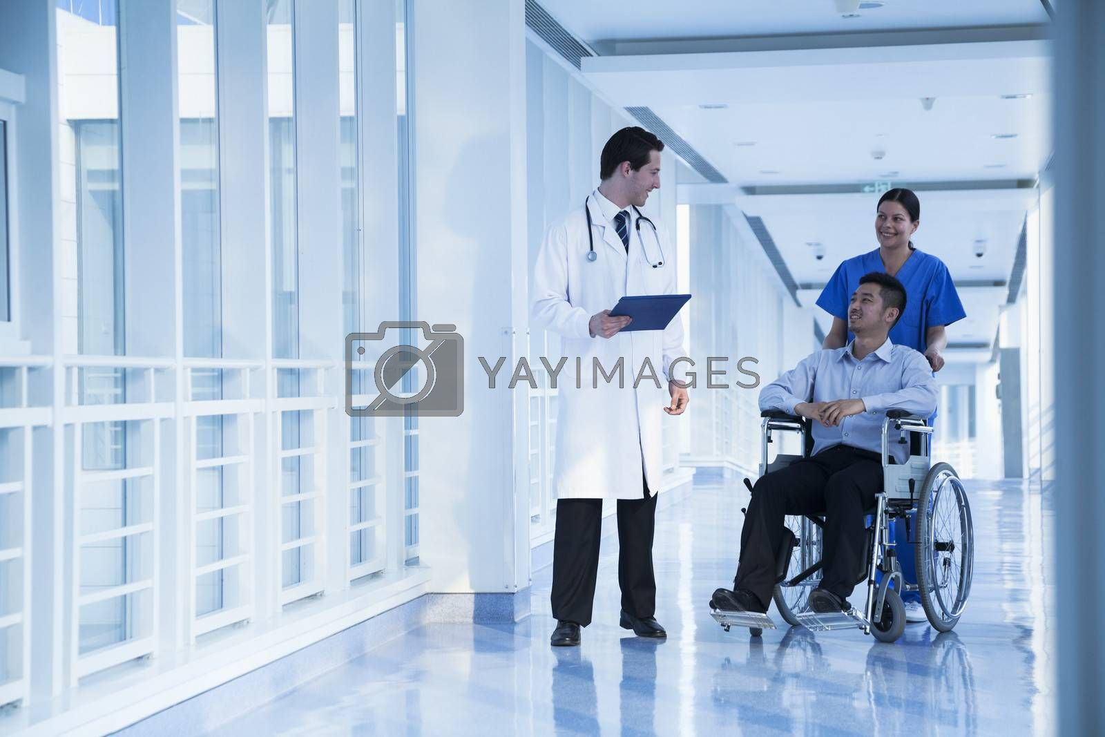 Smiling female nurse pushing and assisting patient in a wheelchair in the hospital, talking to doctor
