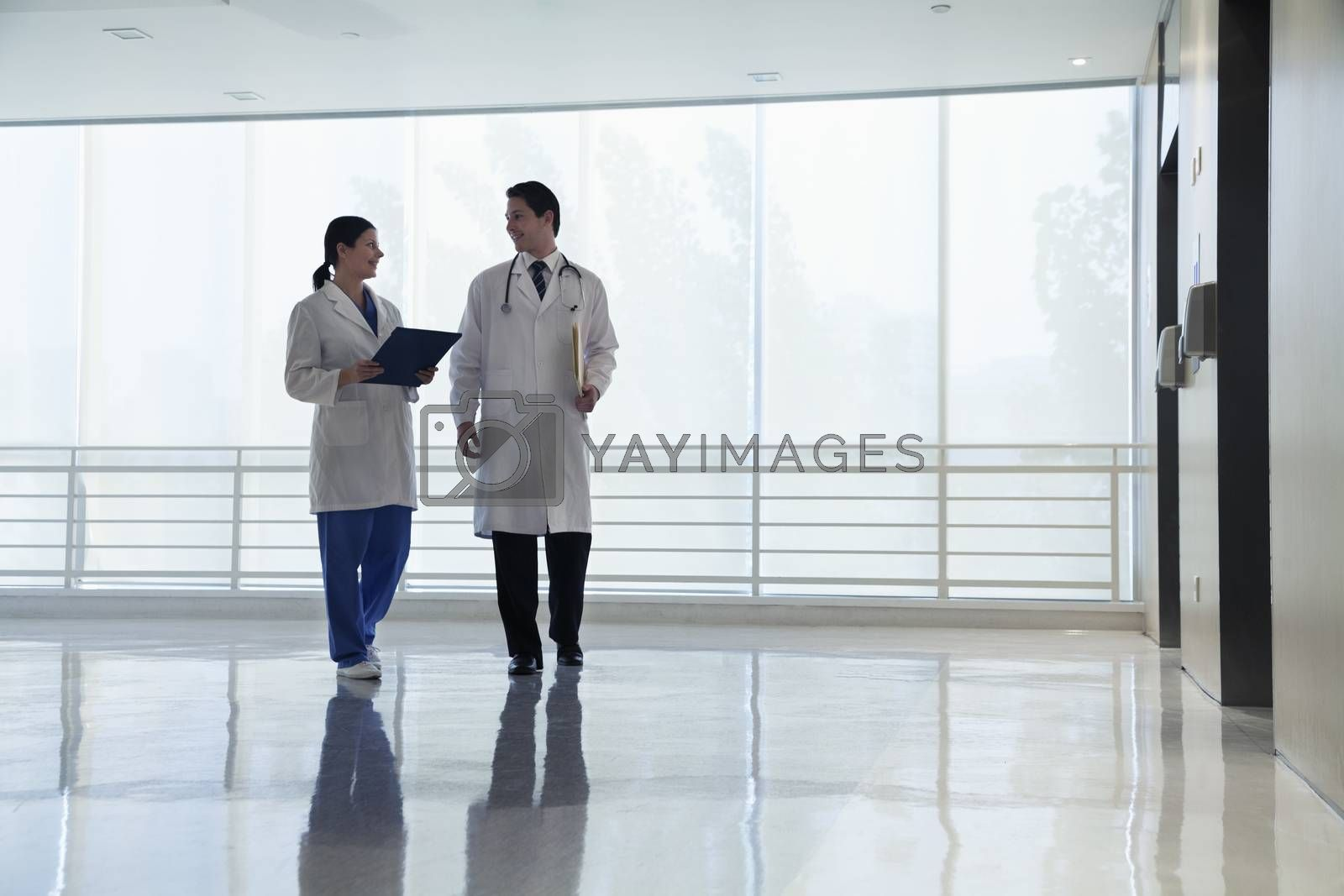 Two doctors walking and smiling in the hospital, full length