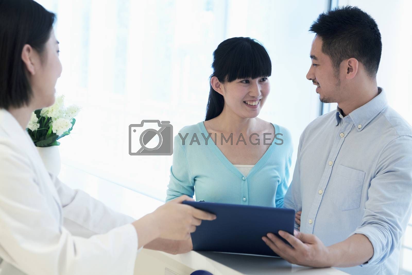 Doctor and smiling couple standing by the counter in the hospital looking at medical record