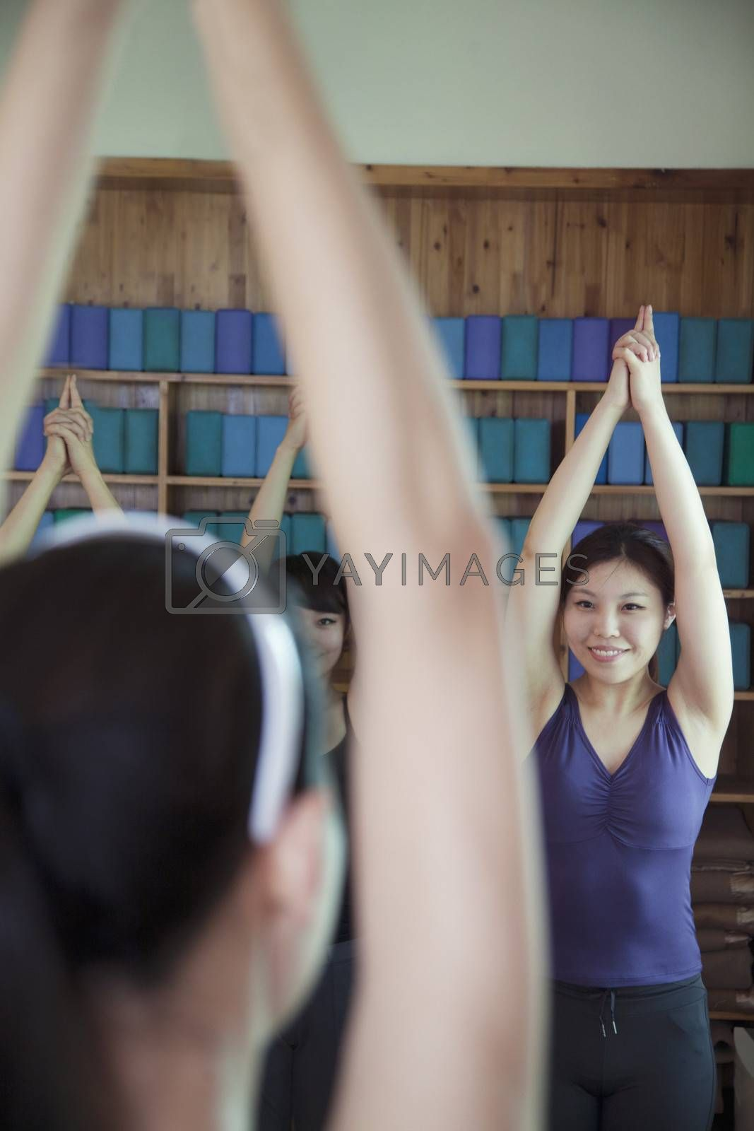 Four young women stretching and doing yoga, over the shoulder view