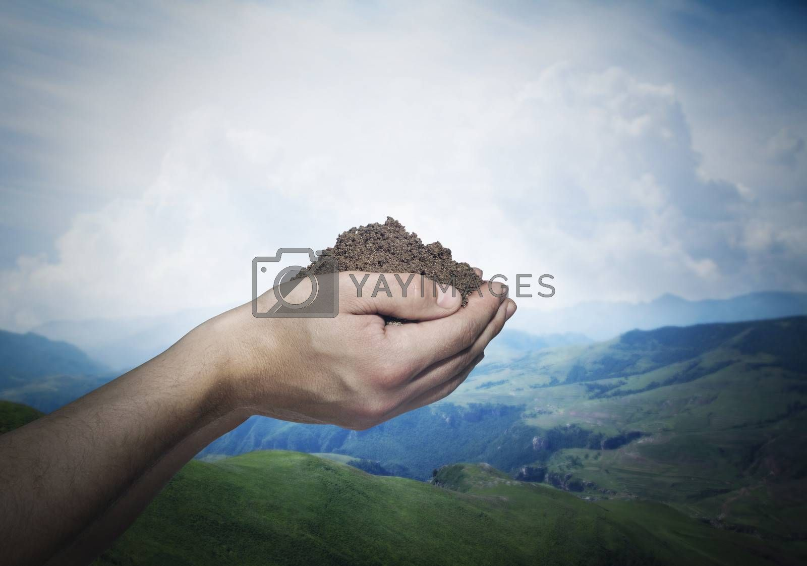 Hands holding a pile of soil with beautiful landscape in the background