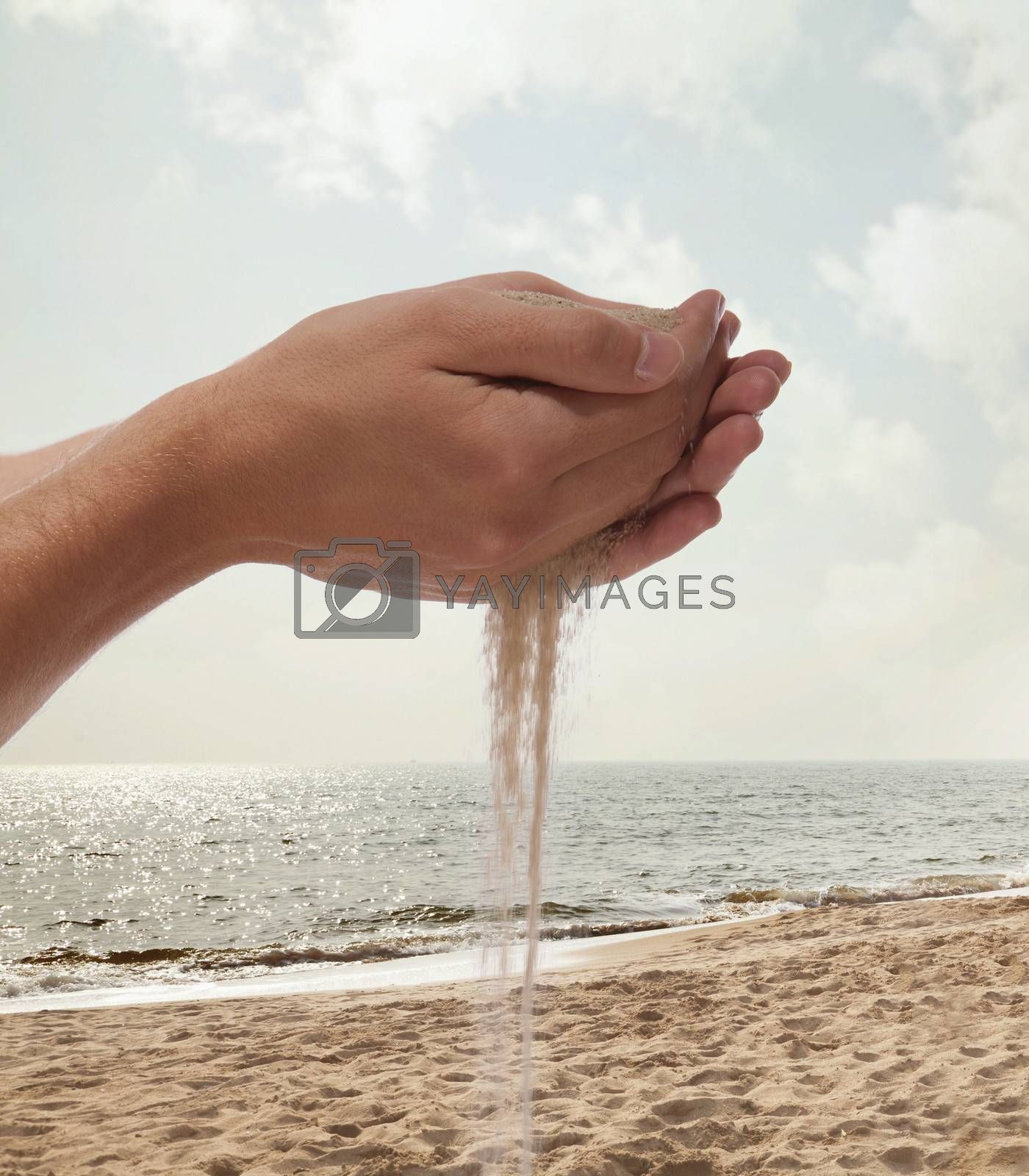 Hands holding and spilling sand with beach in the background
