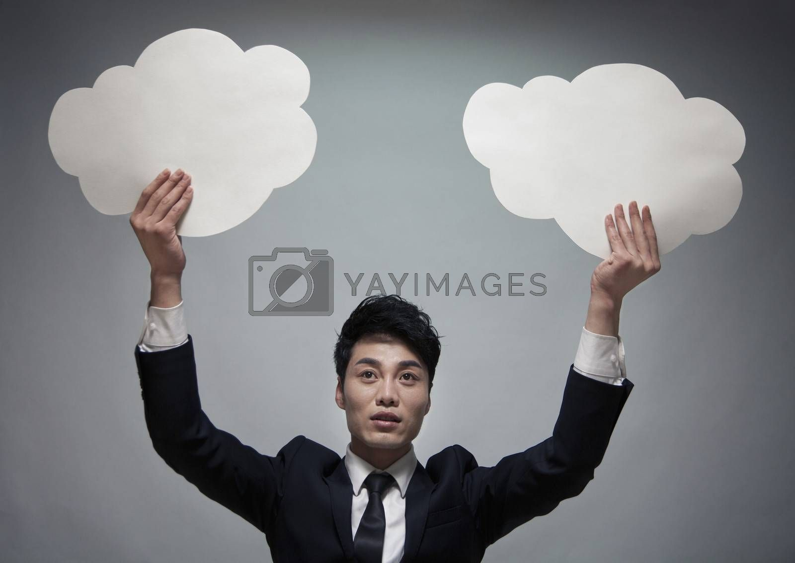 Businessman holding two paper clouds, studio shot