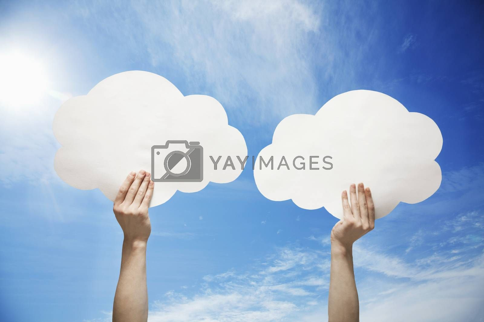Person holding two cut out paper clouds against a blue sky with clouds