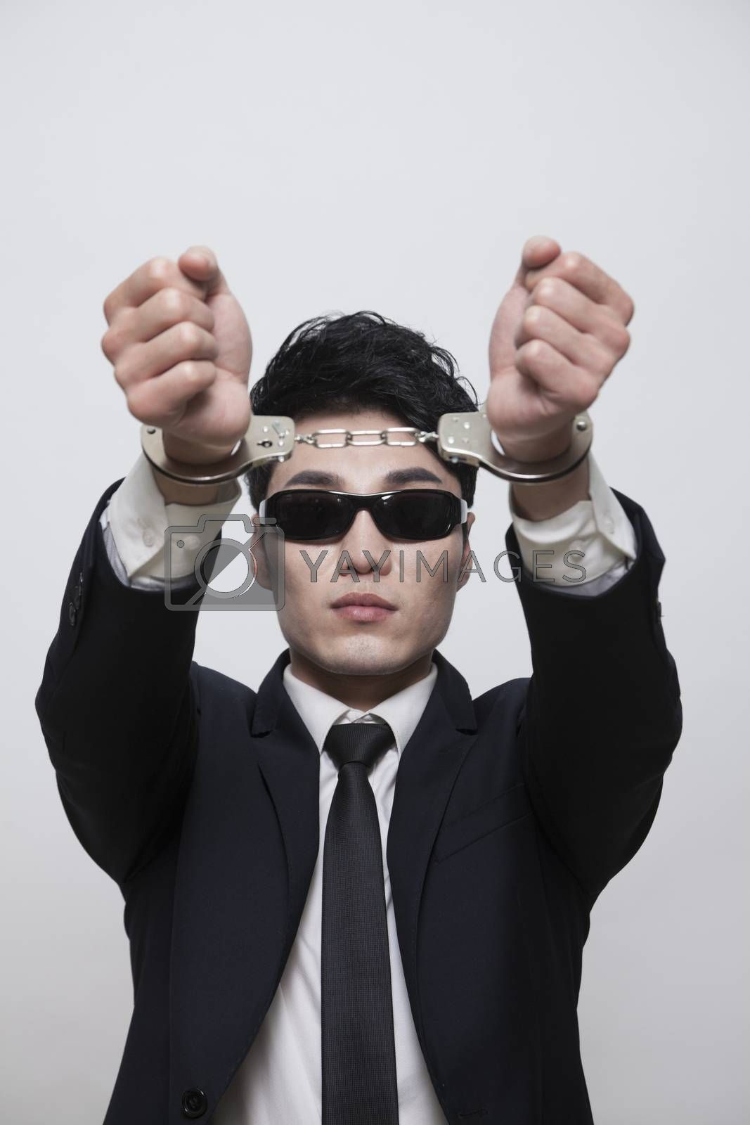 Cool businessman with sunglasses in handcuffs, studio shot