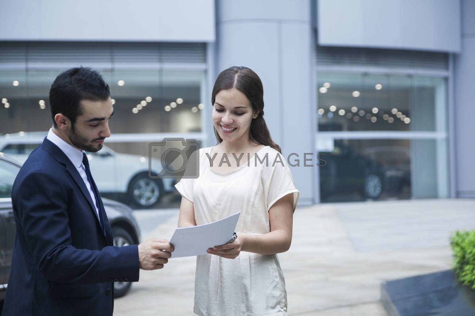 Car salesman and young woman looking over the paperwork at a car dealership