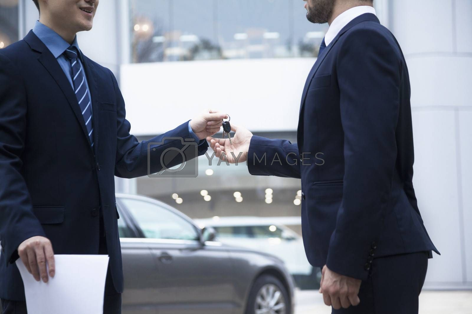Car salesman handing over the keys for a new car to a young businessman