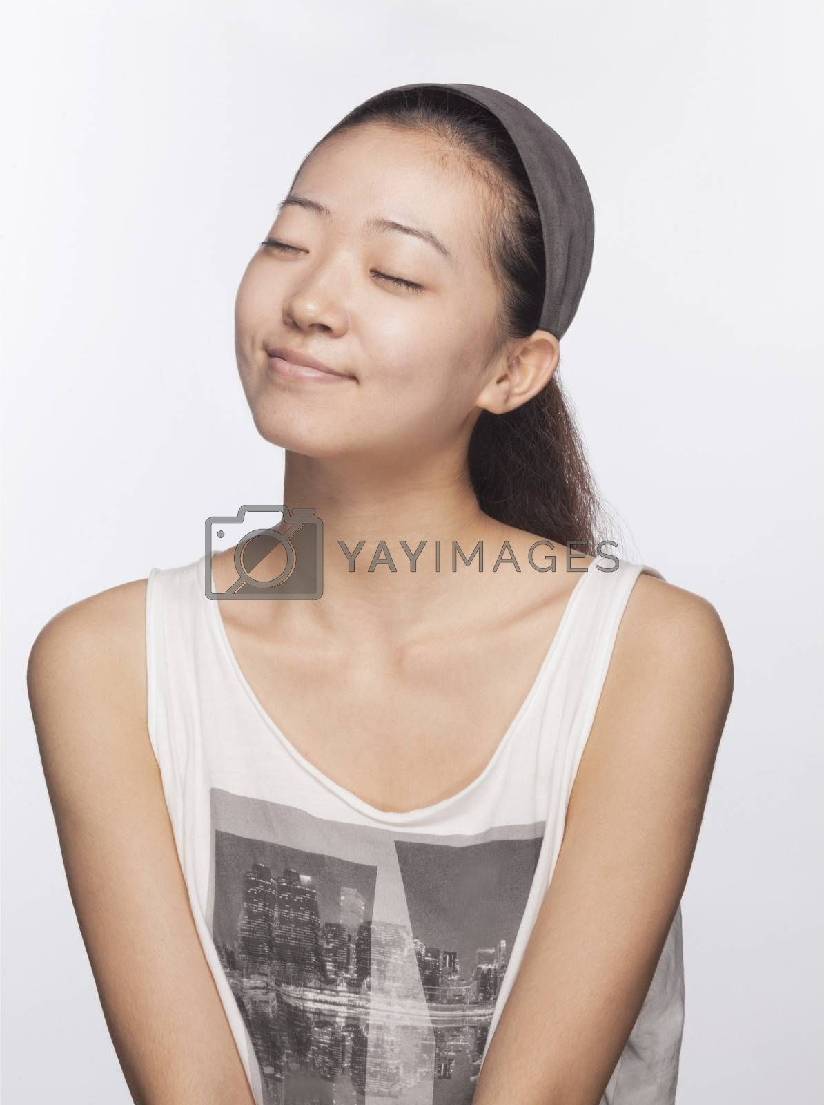 Smiling young woman with eyes closed, studio shot
