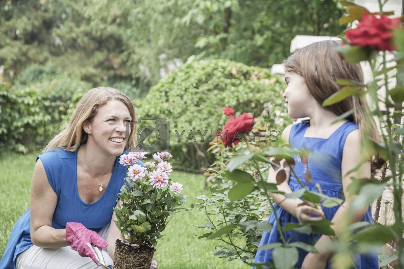 Smiling mother and daughter gardening flowers in the garden