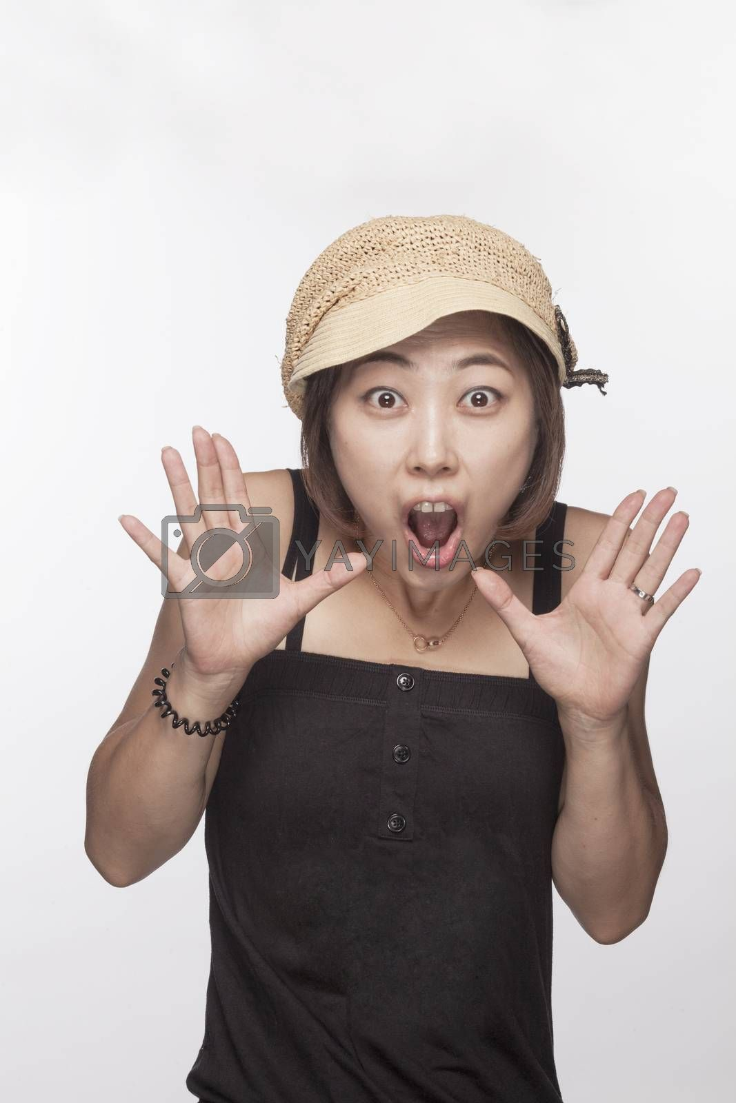 Portrait of surprised woman with hands raised, studio shot