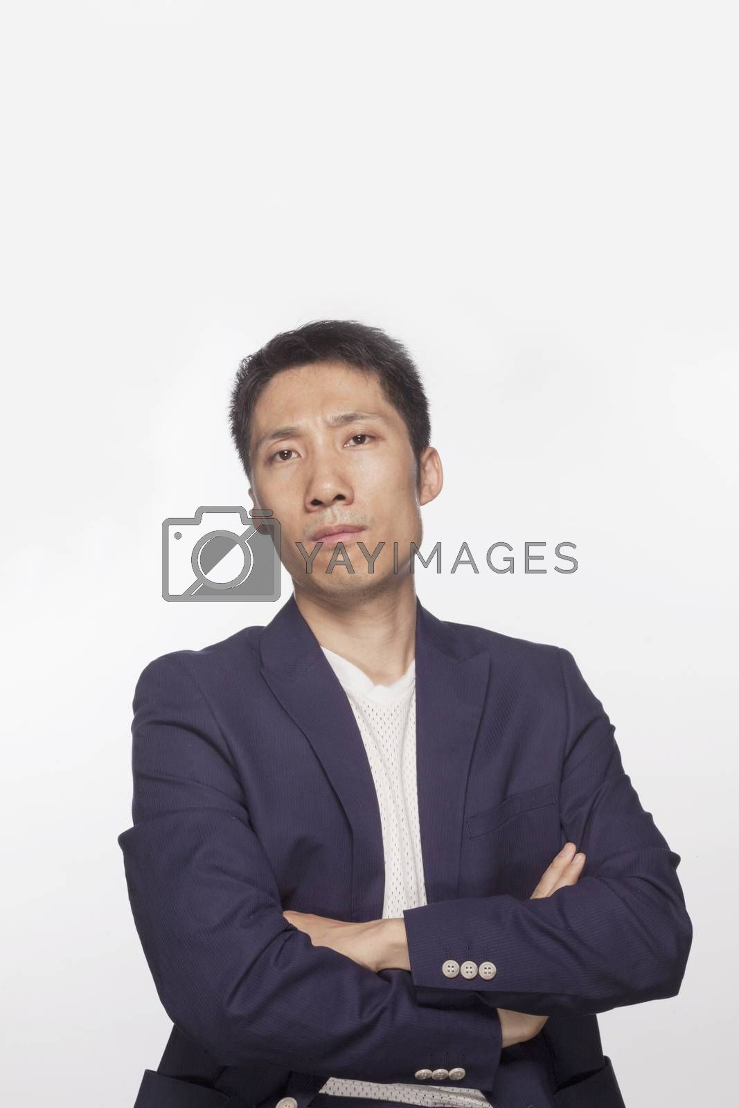 Portrait of serious man with arms crossed looking at camera, studio shot