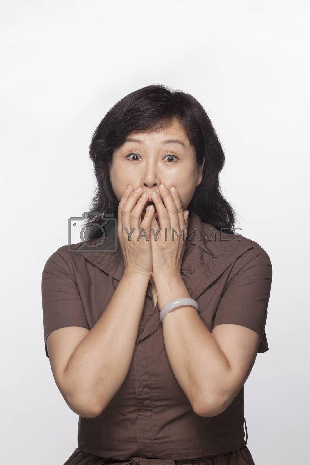 Portrait of shocked and surprised woman with hands covering her mouth, studio shot