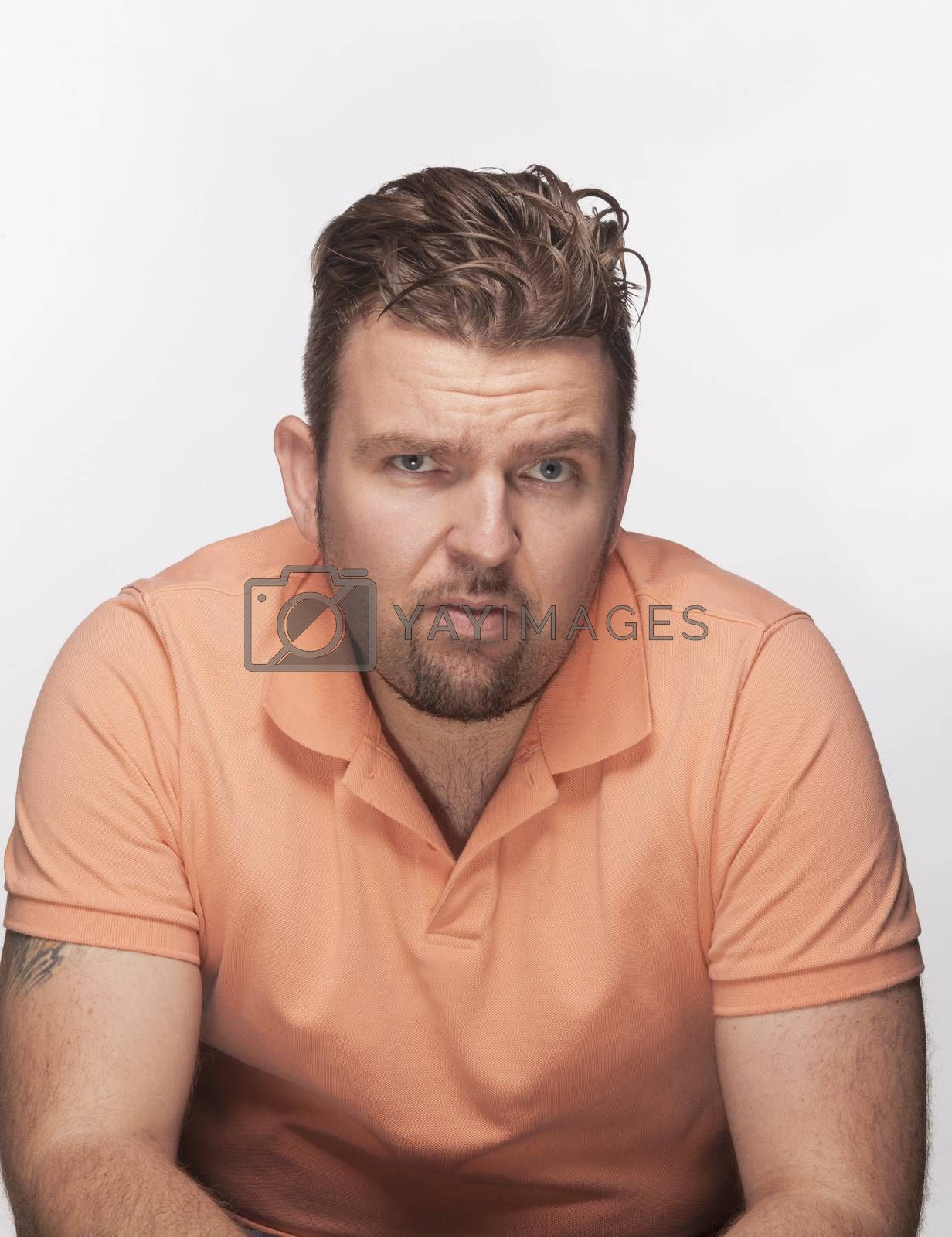 Serious man in orange shirt looking at camera, studio shot